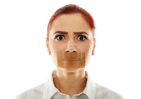 Muted businesswoman with adhesive tape over her mo...