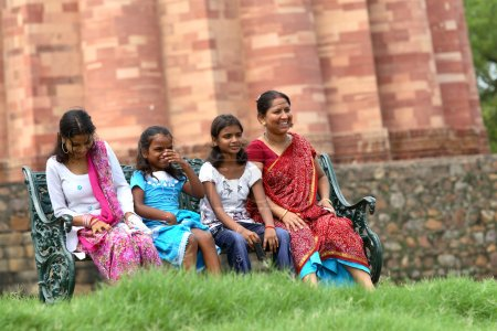 Indian women and girls sitting on bench