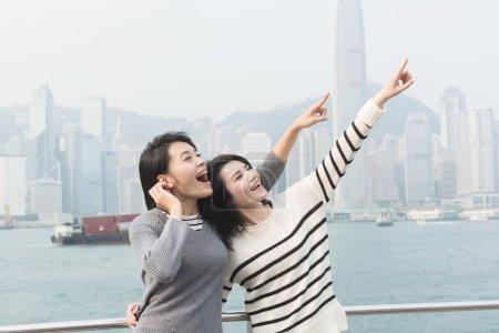 Photo pour Asiatiques jeunes filles heureuses voyageant au port de Victoria, Hong Kong, Asie . - image libre de droit