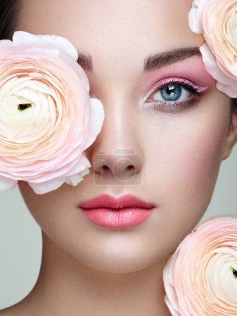 Photo pour Portrait de belle jeune femme aux fleurs. Femme brune avec maquillage de luxe. Une peau parfaite. Des cils. Fard à paupières cosmétique - image libre de droit