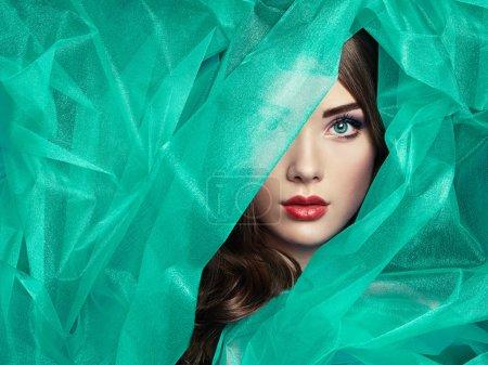 Fashion photo of beautiful women under turquoise veil
