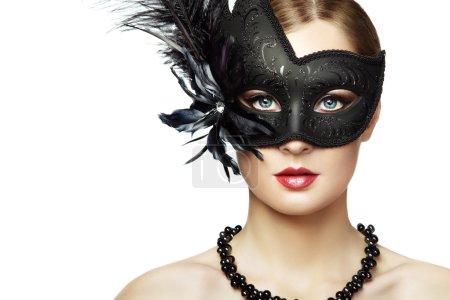 Beautiful young woman in black mysterious venetian mask