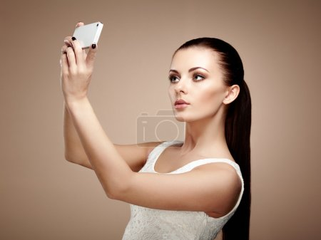 Beautiful young woman taking selfie