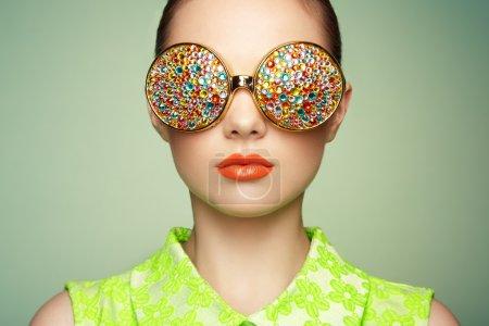 Photo pour Portrait de belle jeune femme avec des lunettes de couleur. Mode beauté. Un maquillage parfait. Décoration colorée. Bijoux - image libre de droit