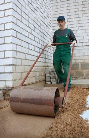 Photo pour Rouleau de compactage du sol manuellement avant de créer un trottoir - image libre de droit