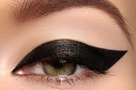 Beautiful female eye with sexy black liner makeup. Fashion big arrow shape on woman's eyelid. Chic evening make-up