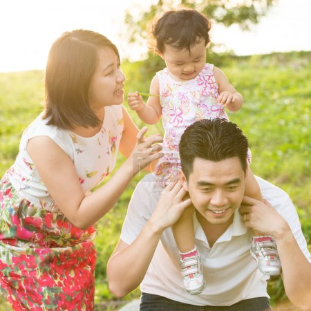 Photo pour Portrait de famille asiatique heureuse jouant au piggyback au parc extérieur pendant le coucher du soleil d'été . - image libre de droit