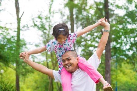 Photo pour Père et fille jouant au piggy dans un jardin extérieur. Heureux style de vie de famille Asie du Sud-Est . - image libre de droit