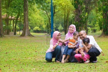 Photo pour Famille heureuse s'amuser à la pelouse verte extérieure. Peuples d'Asie du Sud-Est mode de vie . - image libre de droit