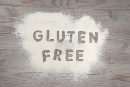 Photo for Word gluten free written in white flour on a old wooden table, vintage tone. - Royalty Free Image