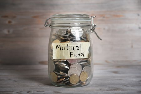 Photo pour Coins in glass money jar with mutual fund label, financial concept. Vintage wooden background with dramatic light. - image libre de droit