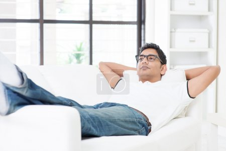 Indian guy resting and daydreaming at home
