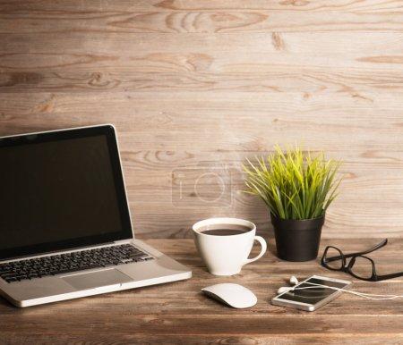 Photo pour Intérieur de bureau en bois, table avec ordinateur portable, tasse de café chaud, souris, lunettes, smartphone, écouteurs et plante en pot, dans un ton vintage dramatique . - image libre de droit