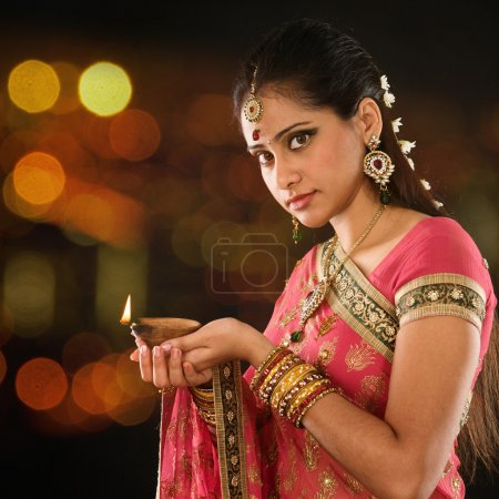 Indian girl hands holding diya lights