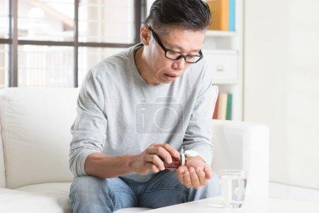 Mature 50s Asian Chinese man eating medicine