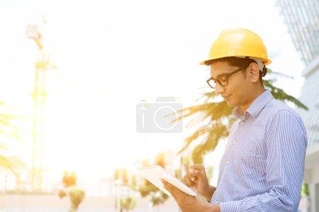 Photo pour Ingénieur indien asiatique d'entrepreneur mâle avec l'ordinateur de fixation de main de chapeau dur retenant l'ordinateur inspectant au chantier de construction, lumière du soleil de matin à l'arrière-plan. - image libre de droit