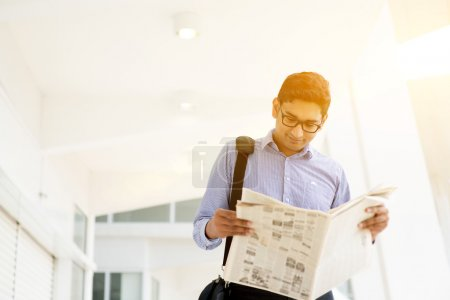 Executive reading newspaper while going to office