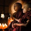 Young novice monks sitting inside a Buddhist templ...