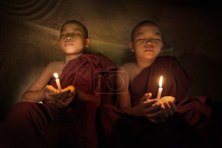 Buddhist novices praying with candlelight