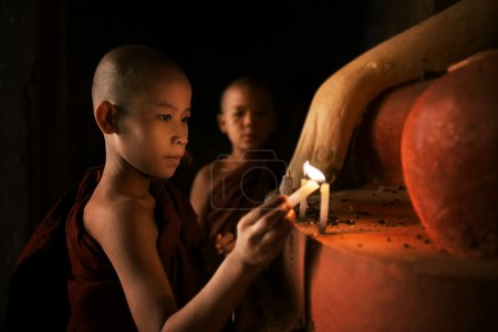 Buddhist novices praying with candlelight in monastery