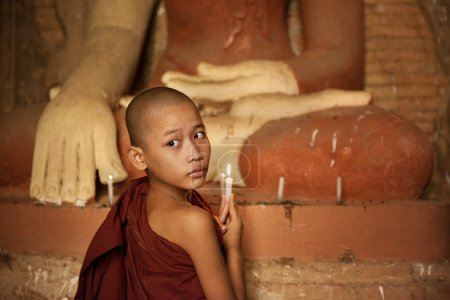 Photo for Portrait of young novice monk praying with candle light inside a Buddhist temple, Bagan, Myanmar. - Royalty Free Image