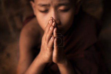 Photo for Young novice monk praying inside Buddhist temple, low light with noise setting, Bagan, Myanmar. - Royalty Free Image