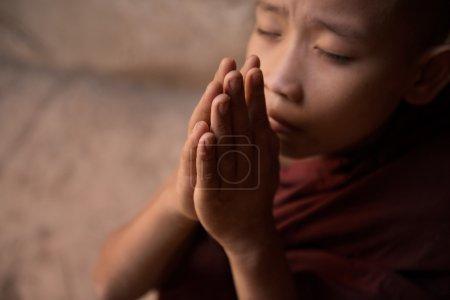 Close up Buddhist novice monks praying