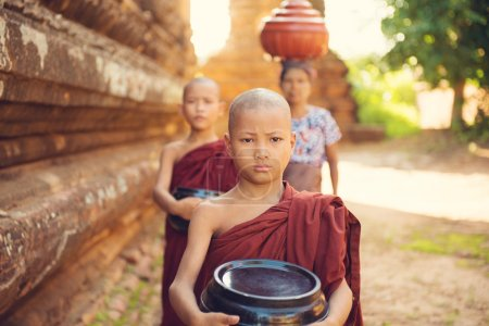 Photo for Southeast Asian young Buddhist monks walking morning alms in Old Bagan, Myanmar - Royalty Free Image