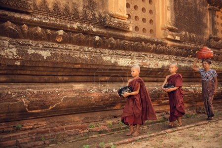 Photo for Southeast Asian young Buddhist novice monks walking morning alms in Old Bagan, Myanmar - Royalty Free Image