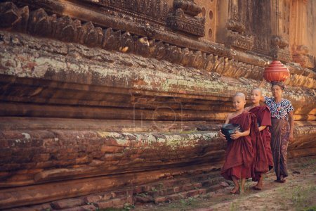 Photo for Young Buddhist novice monks walking morning alms in Old Bagan, Myanmar - Royalty Free Image
