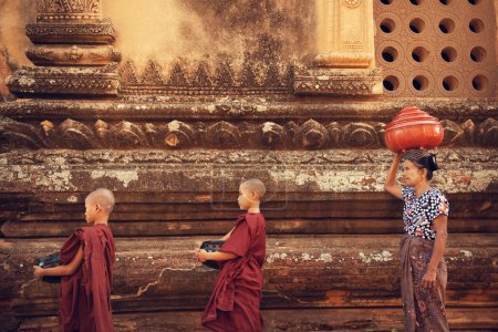 Photo for Buddhist novice monks walk to collect alms and offerings at old bagan, Myanmar. This procession is held every morning. - Royalty Free Image