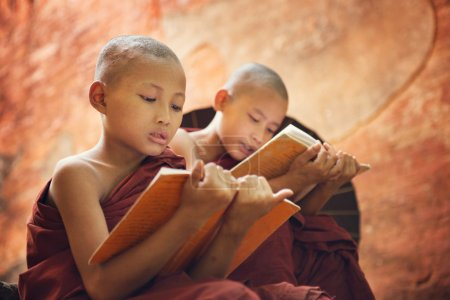 Photo for Young Buddhist novice monk reading and study outside monastery, Myanmar. - Royalty Free Image
