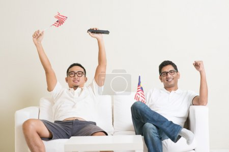 Malaysian men watching sports on tv