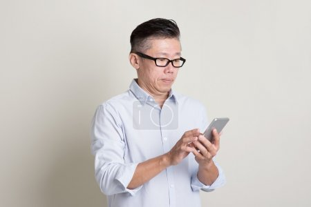 Photo for Portrait of single mature 50s Asian man in casual business playing smartphone, standing over plain background with shadow. Chinese senior male people. - Royalty Free Image
