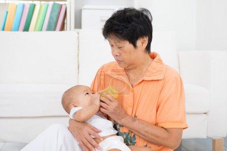Nanny bottle feeding baby