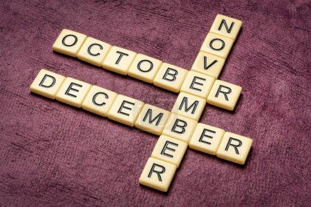 Photo pour Mots croisés octobre, novembre et décembre en carreaux de lettre ivoire contre papier écorce texturé fait main, concept de calendrier - image libre de droit