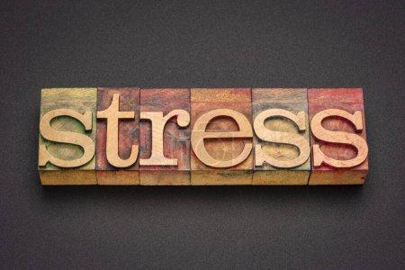 Stresswort abstrakt im Buchdruck Holzart vor schwarzem Acryl-Hintergrund, Arbeits-, Gesundheits- und Lifestylekonzept