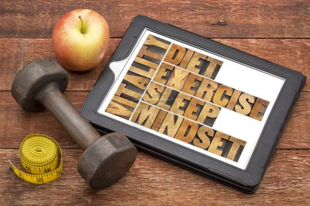 Photo for Diet, sleep, exercise and mindset - vitality concept - abstract in vintage letterpress wood type on a digital tablet with a dumbbell, apple and tape measure - Royalty Free Image
