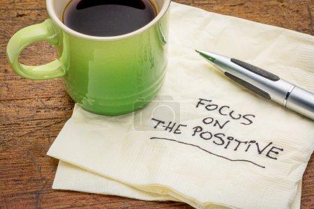 Photo pour Mettre l'accent sur le positif - mots motivants écrits à la main sur une serviette avec une tasse de café expresso - image libre de droit