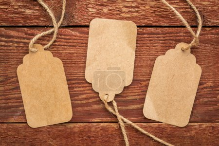 Photo for Three blank paper price tags with a twine against planks of rustic barn wood - Royalty Free Image