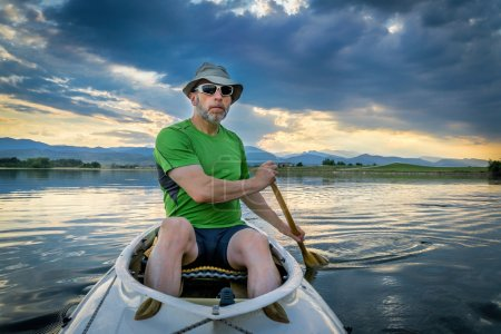 Photo for Senior male paddling an expedition canoe on lake at dusk with Front Range of Rocky Mountains in background - Royalty Free Image