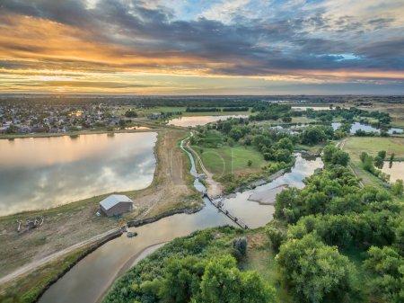 Photo pour Vue aérienne du lever du soleil sur la rivière Cache la Poudre avec barrages de dérivation, fossés d'irrigation et étangs, Windsor, Colorado - image libre de droit