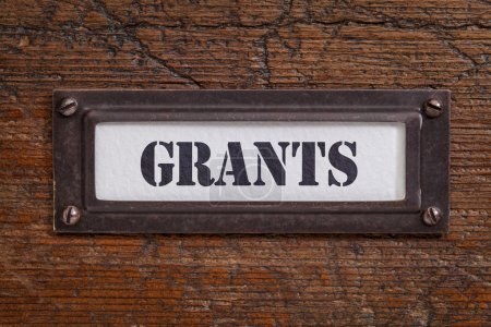 Photo for Grants  - file cabinet label, bronze holder against grunge and scratched wood, financial concept - Royalty Free Image
