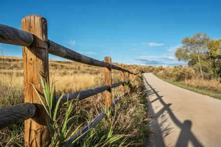 Photo for Wooden fence with a shadow and a  bike trail  - Poudre River Trail in northern Colorado near Windsor. It is a  paved path  extending more than 20 miles between Timnath and Greeley. - Royalty Free Image