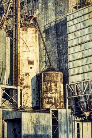 Photo pour Arrière-plan industriel avec effet de texture grunge - extérieur de l'ancien élévateur à grain abandonné avec tuyaux, conduits, échelles et goulottes - image libre de droit