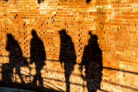 People walking, casting shadows on a wall
