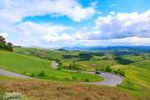 Road rural landscape of Tuscany and green rolling hills near Vol