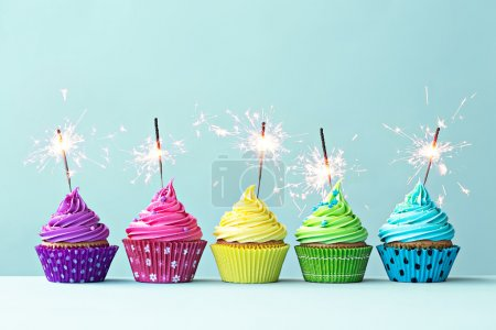 Photo for Row of colorful cupcakes with sparklers - Royalty Free Image