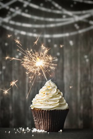Photo for Cupcake with sparkler against a wooden background - Royalty Free Image