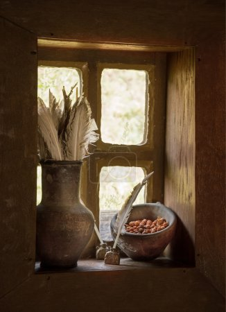Vintage stilllife with feathers in jug and berries on window